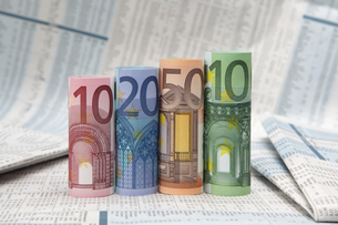 rolled up euro bills on financial newspaperの写真素材 [FYI00702257]