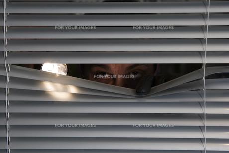 burglar with a flashlight looking through a windowの素材 [FYI00702277]