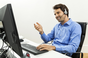attractive young man with headset in the office customer service operatorの写真素材 [FYI00702713]