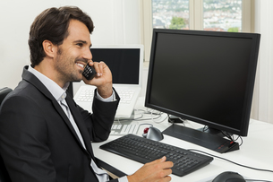 successful businessman sitting in the office and on the phoneの写真素材 [FYI00702714]