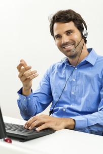 attractive young man with headset in the office customer service operatorの写真素材 [FYI00702716]