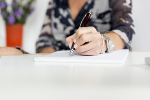 hand (woman) writing with pen and notepadの写真素材 [FYI00704260]