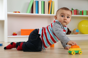 sweet baby playing with toy car in the childrenの写真素材 [FYI00704819]