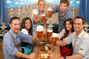 group sits happily on beer tableの写真素材 [FYI00706036]