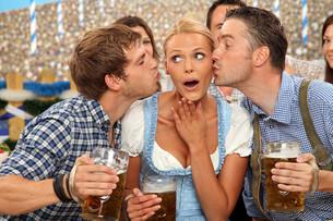 woman gets kisses at oktoberfestの写真素材 [FYI00706063]