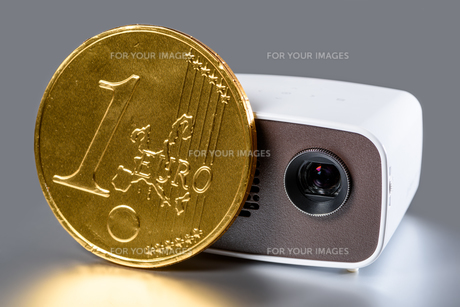 minibeamer with gold euro coin for size comparison mirror on a silver backgroundの写真素材 [FYI00706927]