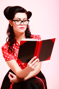 retro. pinup girl in eyeglasses reading bookの写真素材 [FYI00706987]