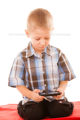 little boy playing games on smartphoneの写真素材 [FYI00706995]