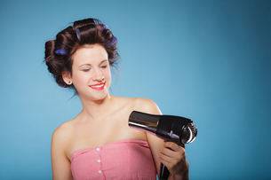 girl with curlers in hair holds hairdreyerの写真素材 [FYI00707004]