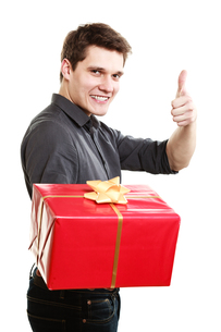holiday. man giving red gift box showing thumb upの写真素材 [FYI00707025]