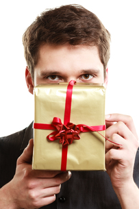 holiday. man giving a golden gift box with ribbonの写真素材 [FYI00707027]