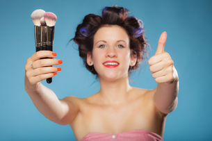 woman in hair rollers holds makeup brushesの写真素材 [FYI00707779]