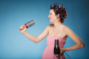 girl with curlers in hair holds hairdreyerの写真素材 [FYI00707780]