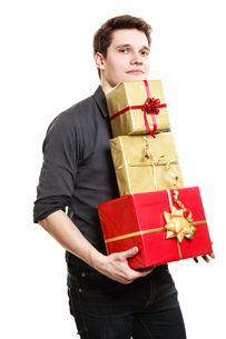 holiday. young man giving presents gifts boxesの写真素材 [FYI00707792]