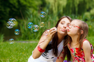 mother and little girl blowing soap bubbles in the park.の写真素材 [FYI00707799]