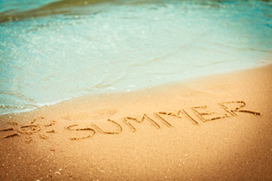 the word summer written in the sand on a beachの写真素材 [FYI00707803]