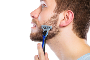 young man with beard holding a razor bladeの素材 [FYI00707826]