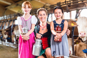 bavarian family with milk cans in the cowshedの写真素材 [FYI00708332]