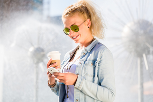woman with phone and coffee at the fountainの写真素材 [FYI00708378]