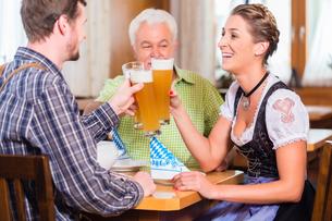 people drinking beer in bavarian pub whiteの写真素材 [FYI00708391]