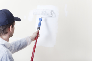 painters sweeps wall with paint roller whiteの写真素材 [FYI00709491]
