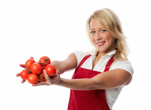 woman with apron presenting a handful of tomatoesの写真素材 [FYI00709645]