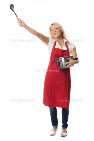 cheerful woman with apron holding a pot and a mixing spoonの素材 [FYI00709656]