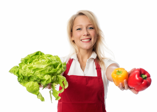 woman with apron presenting a head of lettuce and peppersの写真素材 [FYI00709686]