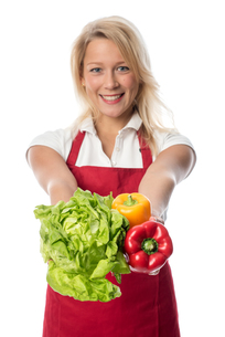woman with apron presenting a head of lettuce and peppersの写真素材 [FYI00709689]