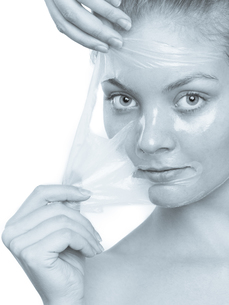 girl removing facial peel off maskの写真素材 [FYI00709727]