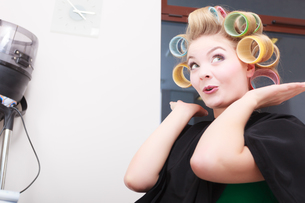 woman in beauty salon,blond girl hair curlers rollers by hairdresser. hairstyle.の写真素材 [FYI00709729]