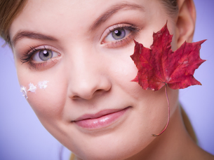 skin care. face of young woman girl with red maple leaf.の写真素材 [FYI00709734]