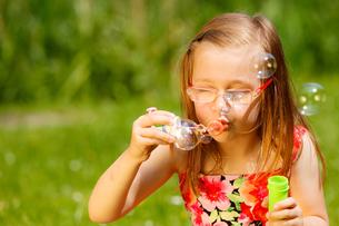 little girl having fun blowing soap bubbles in the park.の写真素材 [FYI00709735]