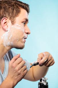 man shaving with razor face profilesの写真素材 [FYI00710148]