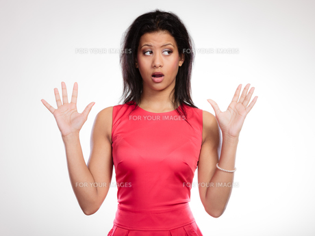 gossip or stress. surprised shocked scared woman. emotional facial expression wide-eyed girl mixed race mouth open hand gesture on grayの写真素材 [FYI00710155]