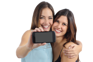 Two friends showing a blank smart phone screenの写真素材 [FYI00710463]