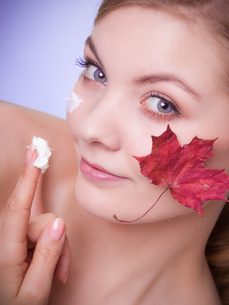 skin care. face of young woman girl with red maple leaf.の写真素材 [FYI00710666]