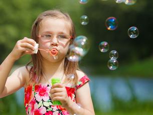 little girl having fun blowing soap bubbles in the park.の写真素材 [FYI00710669]