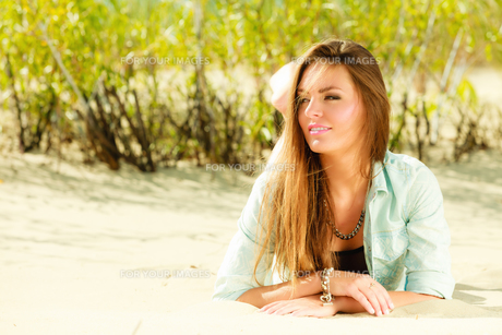 young woman lying on grassy duneの素材 [FYI00710678]