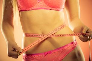 woman measuring her waistlineの写真素材 [FYI00710932]