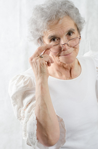 old woman looking over her glassesの素材 [FYI00711121]