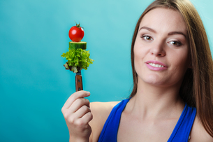 woman holding fork with vegetablesの写真素材 [FYI00711850]