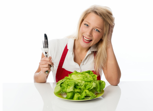 blond woman holding a cutlery and presents a lettuceの写真素材 [FYI00712167]
