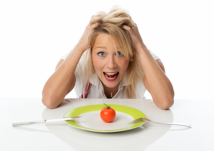 blonde woman sits in front of a plate with a tomatoの写真素材 [FYI00712174]