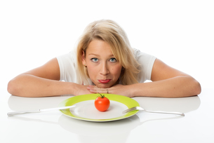 blonde woman with a tomato on the plateの写真素材 [FYI00712177]