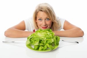 blonde woman presenting a head of lettuceの写真素材 [FYI00712178]