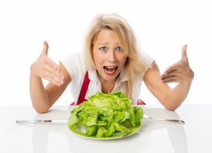 blonde woman presenting a lettuceの写真素材 [FYI00712179]