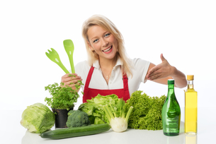 blonde woman presenting lettuce and herbsの写真素材 [FYI00712188]