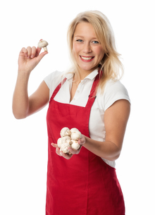 housewife in apron holding a handful of mushroomsの写真素材 [FYI00712223]