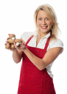 housewife in apron holding a handful of mushroomsの写真素材 [FYI00712227]
